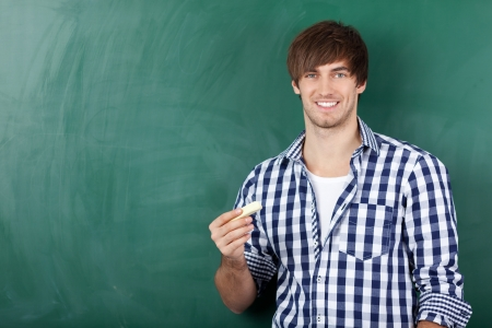 Portrait of handsome young male student in front of chalkboard Stock Photo - 21204566