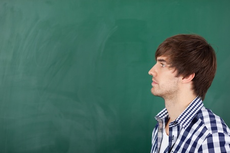 incertitude: Portrait of handsome young male teacher thinking in front of chalkboard