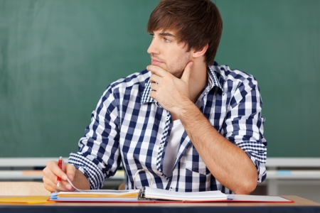 incertitude: Portrait of thinking male teacher at desk against chalkboard