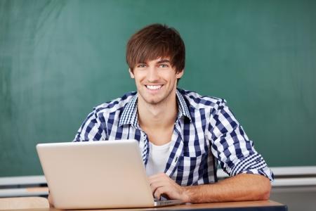 黒板に対しての机に座ってのラップトップでハンサムな若い男性教師の肖像