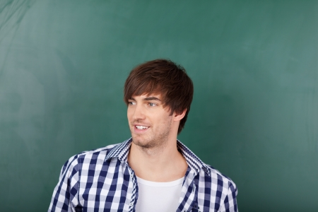 Portrait of handsome young male teacher in front of chalkboard Stock Photo - 21204573