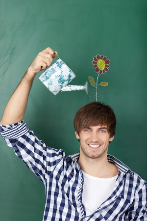 Portrait of handsome young male student holding watering can with flower drawn on chalkboard representing growth of ideas photo