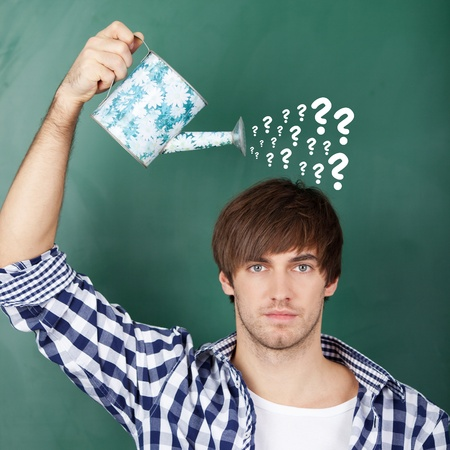 Portrait of young male student holding watering can with question marks on chalkboard representing confusion Stock Photo - 21204576