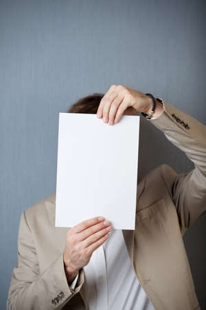 obscurity: Young businessman holding blank paper in front of face against blue wall