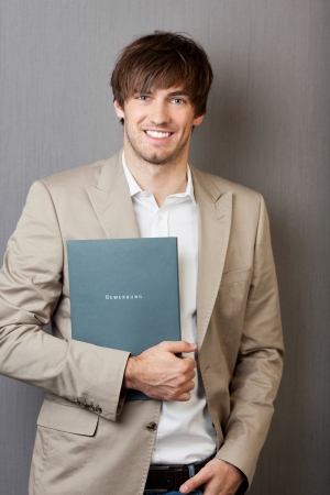 letter of application: Portrait of handsome young businessman holding application file against grey wall Stock Photo