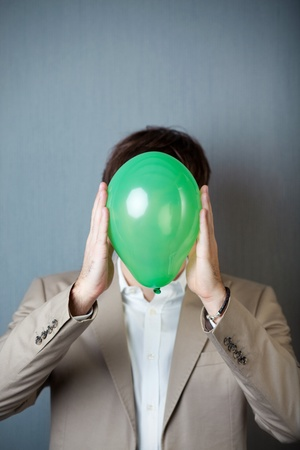 obscurity: Young businessman holding balloon in front of face while standing against blue wall
