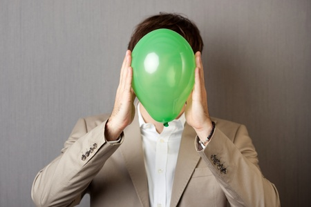 obscurity: Young businessman holding green balloon in front of face Stock Photo