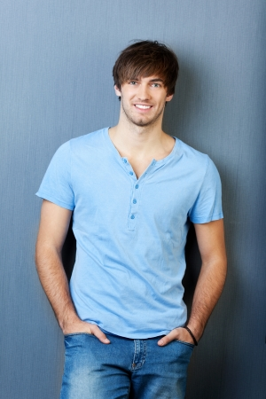 textspace: Portrait of confident young man with hands in pocket standing against blue wall