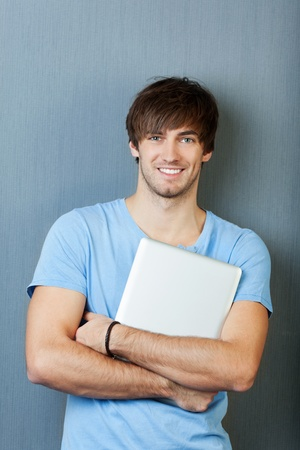 relaxed business man: Portrait of confident young man laptop standing against blue wall Stock Photo