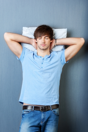 Handsome young man with hands behind head sleeping on blue wall photo