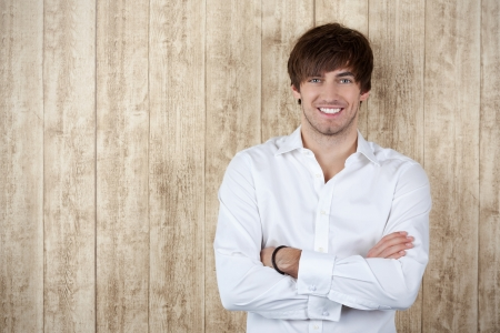 Portrait of confident young businessman with arms crossed standing against wooden wall photo
