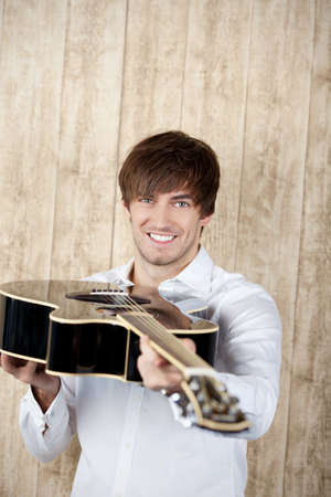 Portrait of handsome young businessman with black guitar standing against wooden wall photo