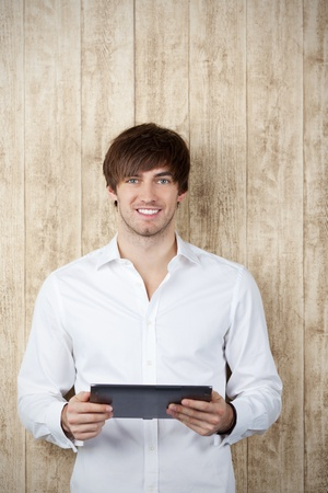 Portrait of smiling young businessman with digital tablet photo