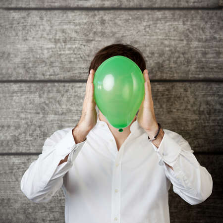 obscured face: Young businessman holding balloon in front of face while standing against wooden wall