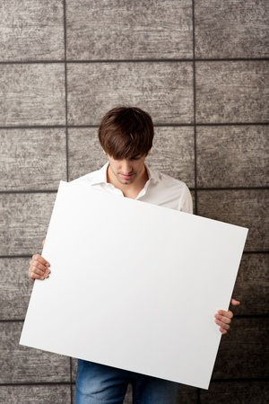 Portrait of young businessman holding billboard in front of wooden wall photo
