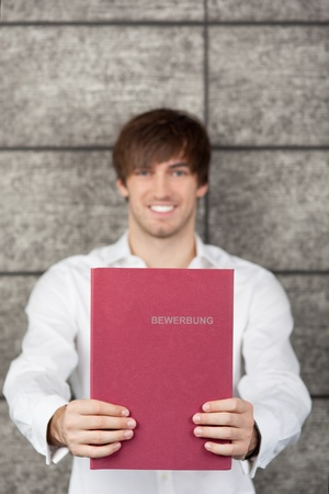 Portrait of smiling businessman holding application file against wooden wall photo