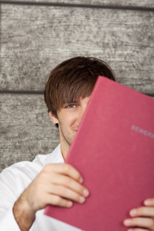 Portrait of businessman holding red application file photo