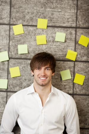 Portrait of confident young businessman with adhesive notes on wooden wall photo