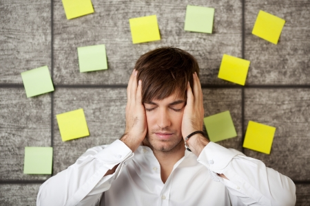 incertitude: Stressed businessman holding his head between hands on wooden background Stock Photo