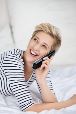 cordless: happy young woman using cordless phone while looking up in bed
