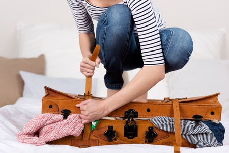 overfilled: Midsection of young woman packing suitcase on bed