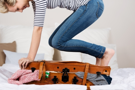 Buik van jonge lachende vrouw verpakking koffer op bed