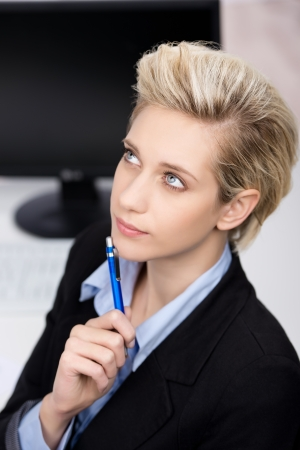Thoughtful young blond businesswoman resting at office desk photo