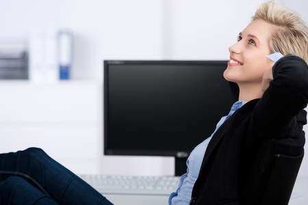 Thoughtful young businesswoman with hands behind head resting at office desk photo