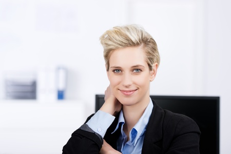 arm chair: Smiling young businesswoman with hand behind head resting at office desk Stock Photo
