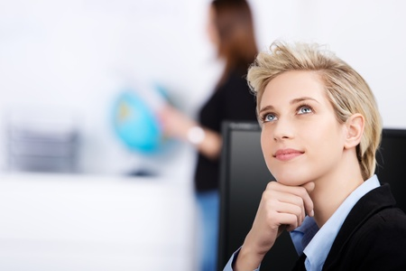 Young businesswoman looking up while thinking in office photo