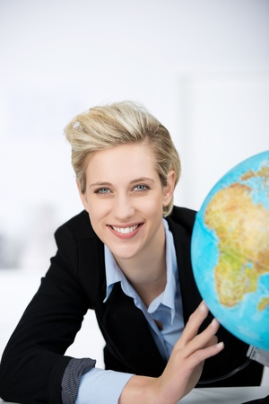 Closeup of smiling businesswoman with a globe in office photo