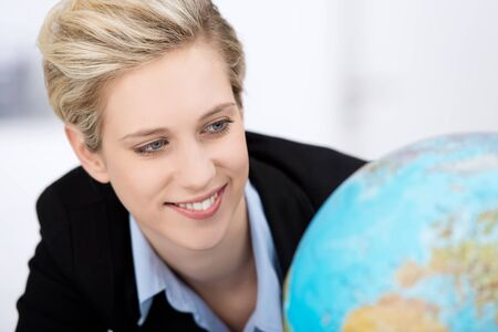 Closeup of young businesswoman looking at globe in office photo