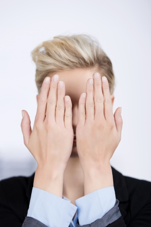 eye protection: Closeup of young businesswoman hiding face with hands in office