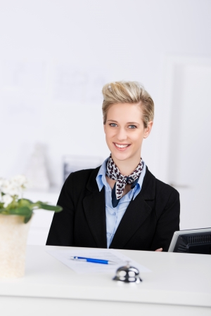 Portrait of confident receptionist smiling at desk photo