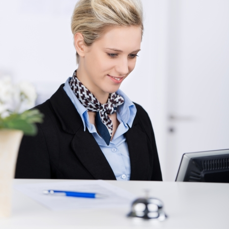 Portrait of confident receptionist smiling while using computer at desk photo