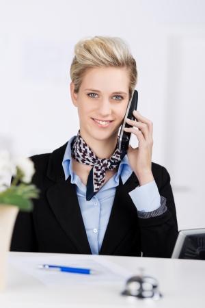 Portrait de réceptionniste confiant souriant tout en utilisant un téléphone sans fil à la réception