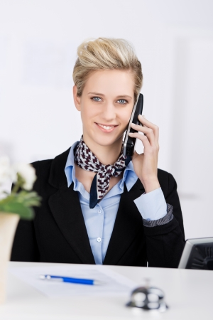 answering phone: Retrato de recepcionista conf�a sonriendo mientras se utiliza el tel�fono inal�mbrico en el escritorio