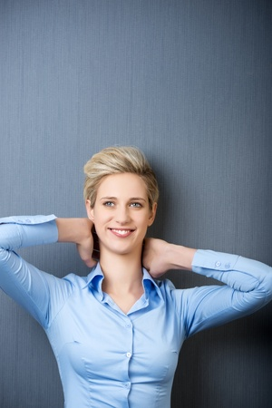woman from behind: Smiling young woman with hands behind head resting against blue wall