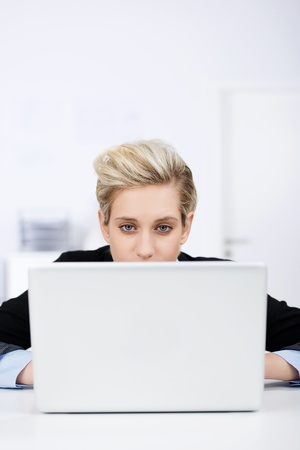 Thoughtful young businesswoman looking at laptop at desk in office Stock Photo