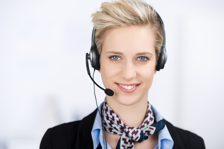 Portrait of young female customer service executive wearing headset while smiling in office photo