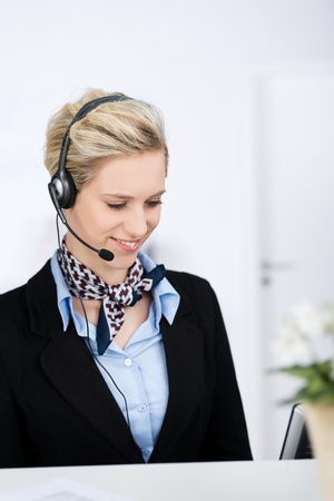 Portrait of young female customer service executive with headset while smiling in office photo