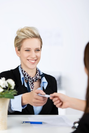 cardkey: Happy young businesswoman receiving cardkey from receptionist at reception Stock Photo