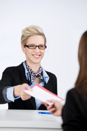 Happy young businesswoman giving traveling documents to receptionist in hotel photo