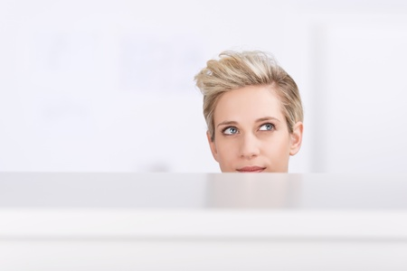 Young businesswoman looking up while daydreaming in office cubicle photo