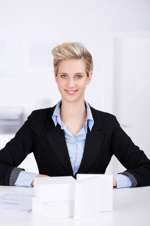 cubicle: Portrait of young female architect sitting at desk in office
