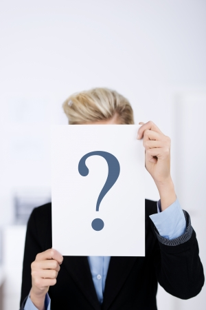 puzzlement: Young businesswoman holding paper with question mark sign in front of face in office Stock Photo
