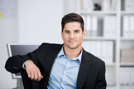 arm chair: Head and shoulders portrait of a handsome smiling businessman sitting looking directly at the camera in his office Stock Photo