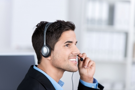 customer service representative: Closeup of young male customer service executive conversing on headset in office Stock Photo