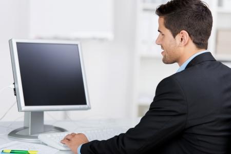Achteraanzicht van de jonge zakenman met behulp van computer op het bureau in het kantoor Stockfoto