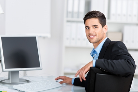 businessman working at his computer: Handsome young businessman sitting at his office in the office working at his computer turning to look at the camera Stock Photo